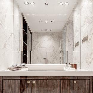 Cette image montre un très grand WC et toilettes design avec un placard à porte plane, des portes de placard en bois brun, un WC séparé, un carrelage beige, des carreaux de céramique, un mur blanc, un sol en bois brun, un lavabo posé, un plan de toilette en quartz, un sol beige et un plan de toilette blanc.