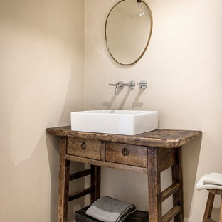 Idée de décoration pour un petit WC et toilettes méditerranéen avec un carrelage beige, un mur beige, un sol en marbre, une grande vasque, un plan de toilette en bois, un sol beige et un plan de toilette marron.