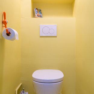 Kleine Moderne Gästetoilette mit flächenbündigen Schrankfronten, gelben Schränken, Wandtoilette, gelben Fliesen, gelber Wandfarbe, Mosaik-Bodenfliesen, Mineralwerkstoff-Waschtisch, gelbem Boden und weißer Waschtischplatte in Sonstige