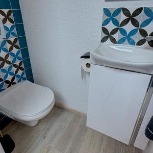 トゥールーズの小さいコンテンポラリースタイルのおしゃれなトイレ・洗面所 (インセット扉のキャビネット、白いキャビネット、壁掛け式トイレ、青いタイル、セラミックタイル、白い壁、セラミックタイルの床、ベッセル式洗面器、グレーの床、フローティング洗面台、板張り天井) の写真