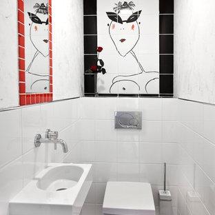 Cette image montre un petit WC et toilettes design avec un WC suspendu, des carreaux de céramique, un mur blanc, un sol en carrelage de céramique et un lavabo suspendu.
