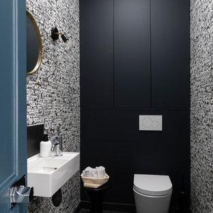 パリの中くらいのコンテンポラリースタイルのおしゃれなトイレ・洗面所 (壁掛け式トイレ、磁器タイルの床、壁付け型シンク、黒い床、マルチカラーの壁) の写真
