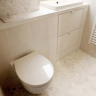 Стильный дизайн: маленький туалет в современном стиле с фасадами с утопленной филенкой, белыми фасадами, инсталляцией, белой плиткой, галечной плиткой, белыми стенами, полом из галечной плитки, врезной раковиной и столешницей из ламината - последний тренд