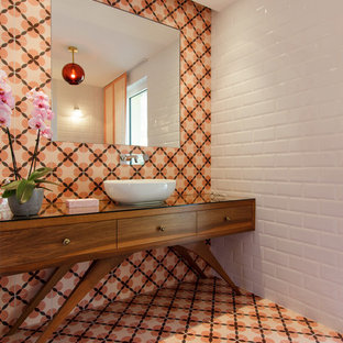 Inspiration for a midcentury cloakroom in Nice with freestanding cabinets, medium wood cabinets, orange tiles, white tiles, mosaic tiles, white walls, mosaic tile flooring, a vessel sink, glass worktops and orange floors.