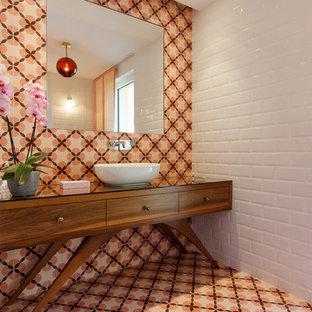 На фото: туалет в стиле ретро с фасадами островного типа, фасадами цвета дерева среднего тона, оранжевой плиткой, белой плиткой, плиткой мозаикой, белыми стенами, полом из мозаичной плитки, настольной раковиной, стеклянной столешницей и оранжевым полом с