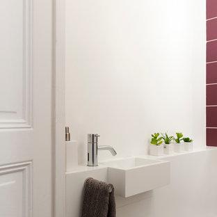 Aménagement d'un WC et toilettes contemporain avec des carreaux de céramique, un mur blanc et un lavabo intégré.