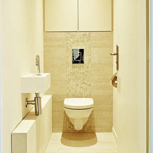 На фото: со средним бюджетом маленькие туалеты в стиле модернизм с фасадами с декоративным кантом, бежевыми фасадами, инсталляцией, бежевой плиткой, плиткой мозаикой, бежевыми стенами, полом из керамической плитки, подвесной раковиной, столешницей из искусственного камня, бежевым полом и белой столешницей