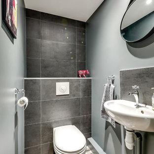 Стильный дизайн: маленький туалет в современном стиле с инсталляцией, синей плиткой, серой плиткой, черной плиткой, цементной плиткой, синими стенами, полом из цементной плитки, столешницей из известняка, разноцветным полом и подвесной раковиной - последний тренд