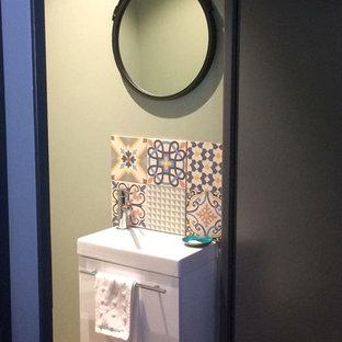 Foto de aseo actual, pequeño, con armarios con paneles lisos, puertas de armario blancas, sanitario de pared, baldosas y/o azulejos multicolor, baldosas y/o azulejos de cemento, paredes verdes, suelo de linóleo, lavabo integrado, suelo beige y encimeras blancas