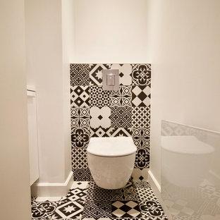 Idee per un piccolo bagno di servizio design con ante a filo, ante bianche, WC sospeso, pistrelle in bianco e nero, piastrelle di cemento, pareti bianche, pavimento in cementine, lavabo sospeso e pavimento multicolore