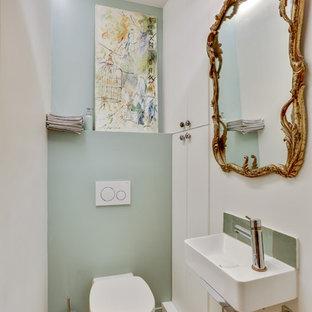 Exemple d'un WC et toilettes chic avec un WC suspendu, un mur vert, un sol en bois brun, un lavabo suspendu et un sol marron.