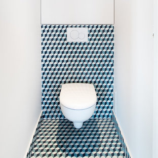 Inspiration for a small contemporary cloakroom in Paris with a wall mounted toilet, cement tiles, white walls, cement flooring, multi-coloured tiles and multi-coloured floors.