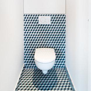 Idée de décoration pour un petit WC et toilettes design avec un WC suspendu, des carreaux de béton, un mur blanc, un sol en carreaux de ciment, un carrelage multicolore et un sol multicolore.