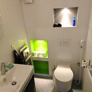 Идея дизайна: большой туалет в современном стиле с открытыми фасадами, зелеными фасадами, инсталляцией, белой плиткой, керамогранитной плиткой, белыми стенами, полом из керамической плитки и монолитной раковиной