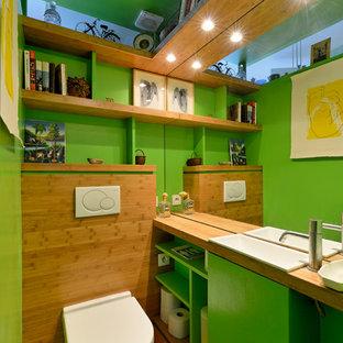 Cette photo montre un WC et toilettes moderne de taille moyenne avec un placard sans porte, des portes de placards vertess, un WC suspendu, un carrelage vert, un mur vert, un sol en bois clair, un lavabo intégré, un plan de toilette en bois et un sol beige.