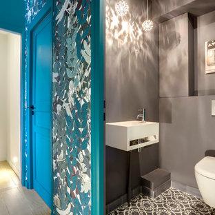 Inspiration pour un WC et toilettes design avec un WC suspendu, un mur gris, un lavabo suspendu et un sol gris.