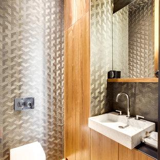Inspiration pour un WC et toilettes design avec un placard à porte plane, des portes de placard en bois brun, un WC suspendu, un mur gris, un sol en bois clair, une vasque, un sol beige et un plan de toilette noir.