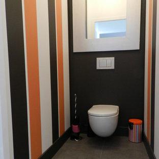 Cette image montre un grand WC et toilettes design avec un WC suspendu, un carrelage gris, des carreaux de céramique, un mur multicolore et un sol en ardoise.