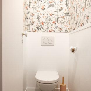 Aménagement d'un petit WC et toilettes moderne avec un placard à porte persienne, des portes de placards vertess, un WC suspendu, un mur blanc, un sol en carreaux de ciment, un sol gris, un plan de toilette blanc, meuble-lavabo encastré et du papier peint.