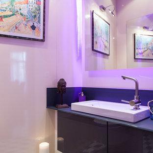 Aménagement d'un petit WC et toilettes classique avec un placard à porte plane, des portes de placard en bois sombre, un WC suspendu, un carrelage gris, des carreaux de céramique, un lavabo intégré, un plan de toilette en verre, un mur beige et un sol en carreaux de ciment.