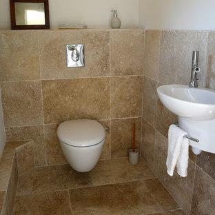 Modelo de aseo bohemio, de tamaño medio, con sanitario de pared, baldosas y/o azulejos beige, baldosas y/o azulejos de travertino, paredes blancas, suelo de travertino, lavabo suspendido, encimera de travertino, suelo beige y encimeras blancas