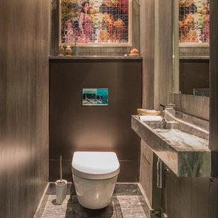 Réalisation d'un grand WC et toilettes design avec une grande vasque, un carrelage gris, un mur gris, un WC suspendu, un sol en marbre et un plan de toilette en marbre.