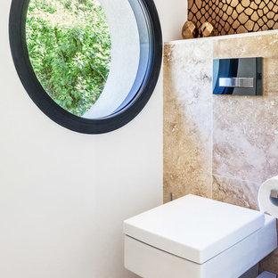 Idée de décoration pour un WC et toilettes design de taille moyenne avec un WC suspendu, un carrelage de pierre, un mur blanc et un sol beige.