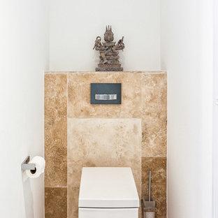 Réalisation d'un petit WC et toilettes asiatique avec un carrelage beige, un mur blanc et un sol marron.
