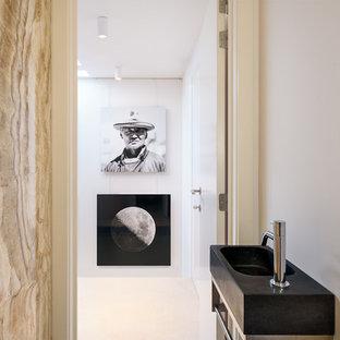 Ispirazione per un bagno di servizio minimal di medie dimensioni con WC sospeso, piastrelle di pietra calcarea, pareti beige, pavimento con piastrelle in ceramica, lavabo sospeso e pavimento beige