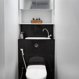 This is an example of a small contemporary cloakroom in Paris with beaded cabinets, a wall mounted toilet, white walls, marble flooring, an integrated sink, tiled worktops and black floors.