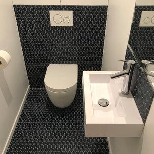 Idee per un bagno di servizio design di medie dimensioni con ante a filo, ante bianche, WC sospeso, piastrelle blu, piastrelle in terracotta, pareti bianche, pavimento in terracotta, lavabo sospeso, top in quarzo composito e pavimento blu
