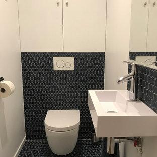 Ispirazione per un bagno di servizio design di medie dimensioni con ante a filo, ante bianche, WC sospeso, piastrelle blu, piastrelle in terracotta, pareti bianche, pavimento in terracotta, lavabo sospeso, top in quarzo composito e pavimento blu