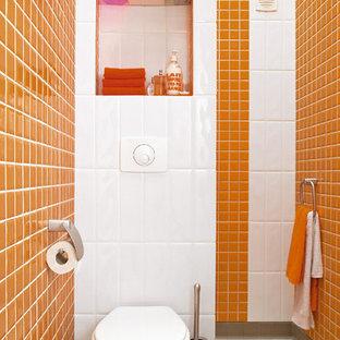 Ejemplo de aseo minimalista, de tamaño medio, con sanitario de pared y parades naranjas