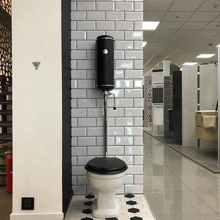 На фото: маленький туалет в стиле ретро с фасадами в стиле шейкер, черными фасадами, биде, серой плиткой, терракотовой плиткой, серыми стенами, полом из цементной плитки, раковиной с несколькими смесителями, столешницей из ламината, разноцветным полом и черной столешницей с