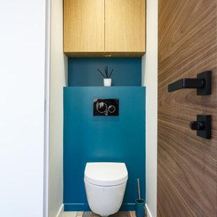 Exemple d'un petit WC et toilettes tendance avec des portes de placard en bois clair, un WC suspendu, un mur bleu, sol en stratifié, un sol multicolore et meuble-lavabo encastré.