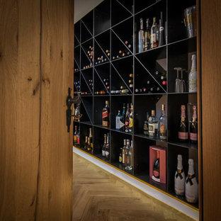 Aménagement d'une grand cave à vin contemporaine avec un sol en bois clair, un présentoir et un sol marron.