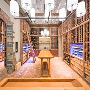 This is an example of an expansive rustic wine cellar in New York with brick flooring, storage racks and red floors.