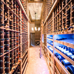 Inspiration for an expansive rustic wine cellar in New York with brick flooring, storage racks and red floors.
