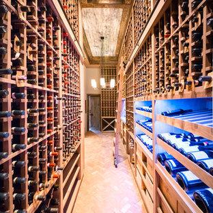 Ejemplo de bodega rústica, extra grande, con suelo de ladrillo, botelleros y suelo rojo