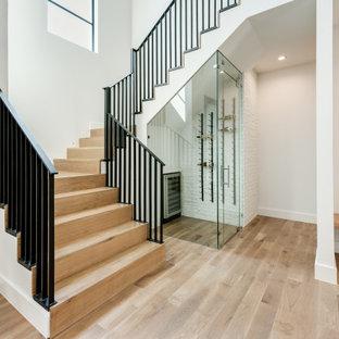 Ispirazione per una piccola cantina design con pavimento in legno massello medio, rastrelliere portabottiglie e pavimento marrone
