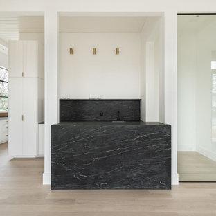 Ejemplo de bodega moderna, de tamaño medio, con suelo de madera clara, vitrinas expositoras y suelo marrón