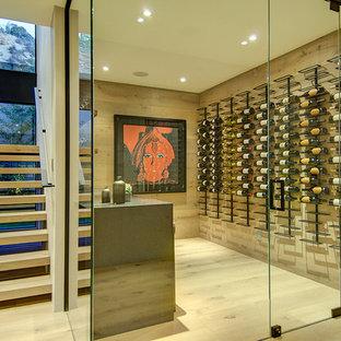 Exemple d'une cave à vin moderne avec un sol en bois clair, un présentoir et un sol blanc.