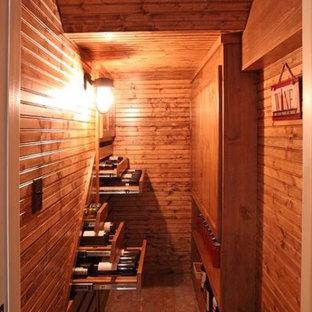 Idée de décoration pour une petit cave à vin avec un sol en travertin, des casiers et un sol marron.