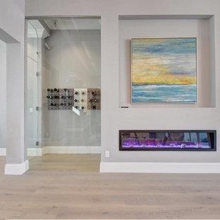 Ejemplo de bodega clásica renovada, de tamaño medio, con suelo de madera clara, botelleros y suelo gris