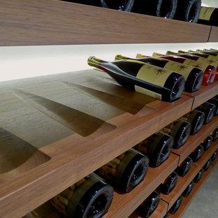 Réalisation d'une petit cave à vin minimaliste avec béton au sol et un présentoir.