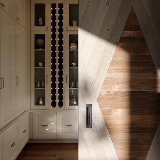 Inredning av en lantlig liten vinkällare, med mellanmörkt trägolv, vindisplay och beiget golv