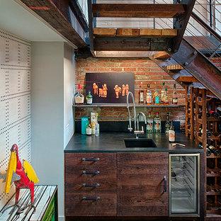 Inspiration för små industriella vinkällare, med mörkt trägolv, vinhyllor och brunt golv