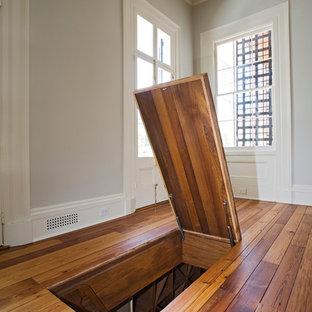 Diseño de bodega clásica, de tamaño medio, con suelo de madera en tonos medios y botelleros de rombos