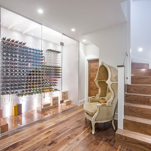 Modelo de bodega contemporánea con suelo de madera en tonos medios, botelleros y suelo marrón