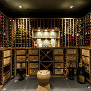 Example of a mid-sized transitional ceramic tile wine cellar design in Surrey with storage racks